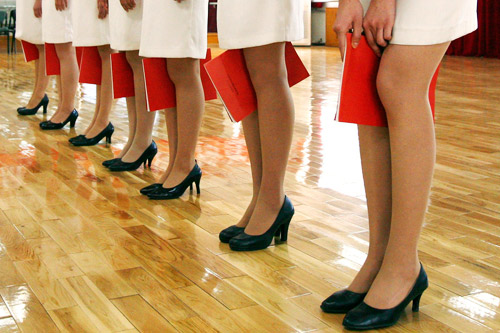 2008 Beijing Olympics hostess girls training standing with legs together using books between knees
