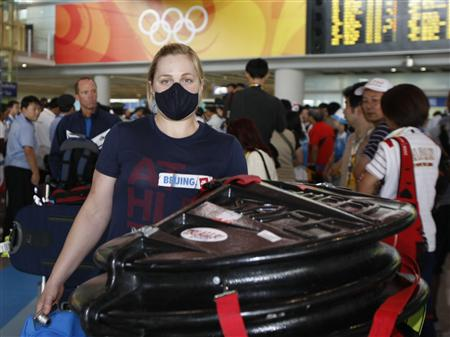 American female cyclist arrives for 2008 Beijing Olympic Games wearing face mask