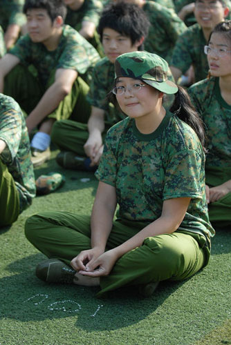 Chinese student improperly wearing hat and writing 'I Love You' on the ground during military training.