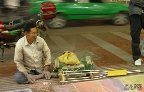 Handicap beggar, one-leg, sitting by his sidewalk chalk art.