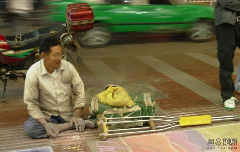 A one-legged handicapped beggar in Guiyang, China crawls on hands creating art with chalk on the streets each day, inspiring pedestrians and Chinese netizens.