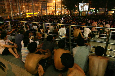 Chinese migrant workers in Chaoyang watching outdoor movie.