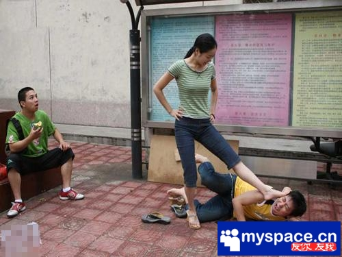A funny picture of a Chinese woman stepping on a man's head while another guy watches in surprise.