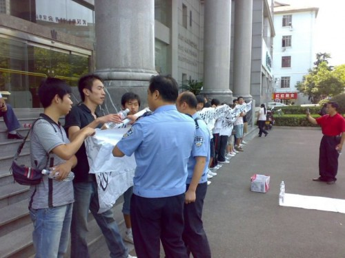 Police in Wuhan try to take banner from university protesters.