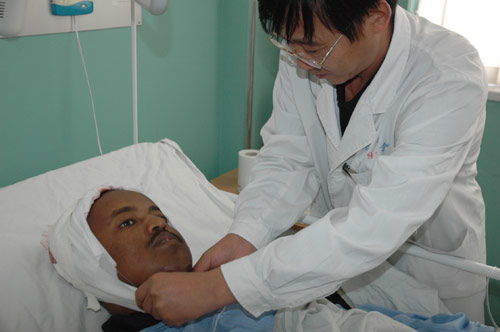Chinese doctor adjusting bandage for patient.