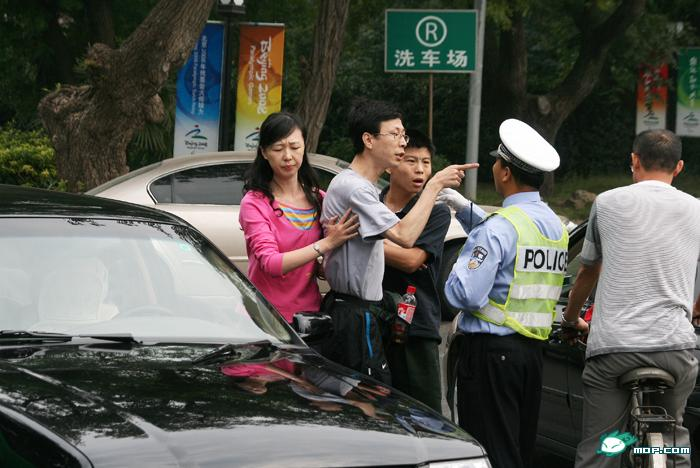 A Nanjing traffic police officer stops a car with black Volkswagen Santana with military license plates for running a red light, using his body to block the car
