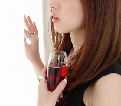 Pretty Asian girl holding glass of wine.