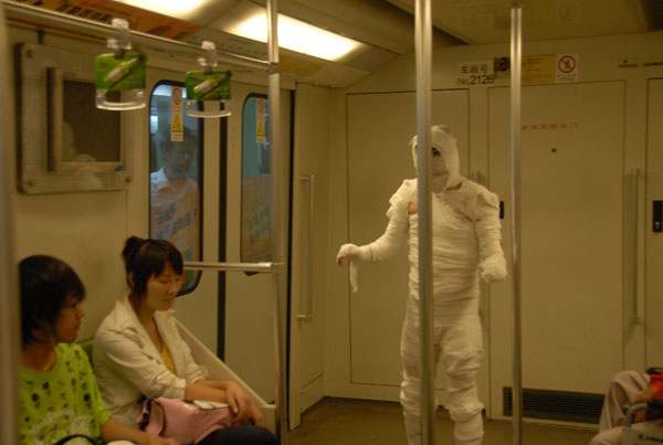 Passengers on Shanghai's Line 2 subway are suddenly startled by a mummy boarding their train. Cameras take pictures as women shy away from this funny mummy.