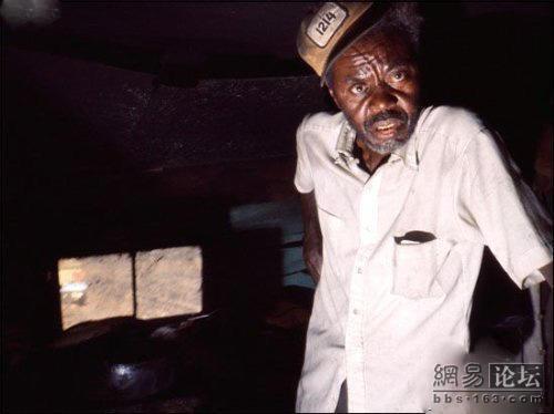 A black man in a white shirt living in a dark house.