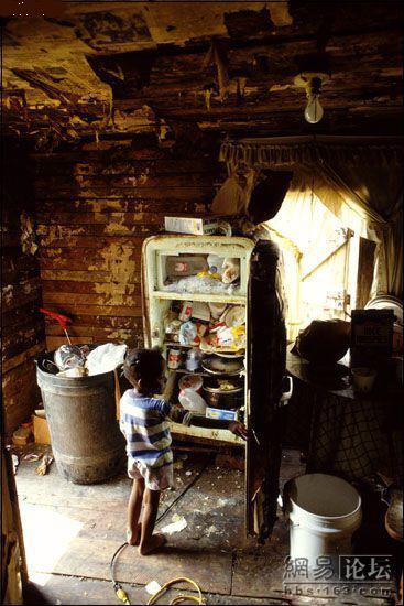 A small black child looks into an old refrigerator filled with leftover food and trash.