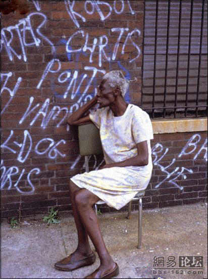 An old, skinny, black woman sitting on a chair next to a brick wall covered with graffitti.