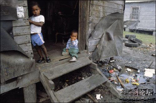 Two small black children living in a shack.