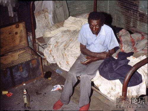 A poor, sick black man sitting on a bed in a messy, dirty room.