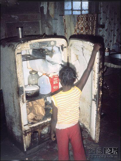 A small black girl looks ino an old refrigerator looking for food in a poor house.