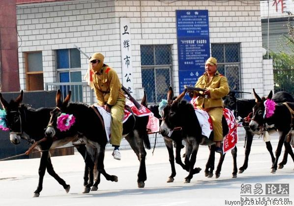 Two fake Japanese soldiers ride on top of two donkeys through the city streets.