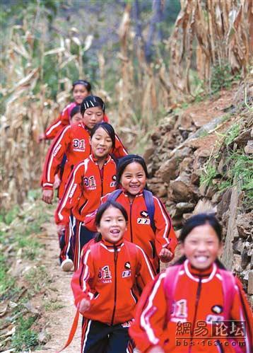 A line of smiling Chinese children wearing red uniforms in rural, mountainous China.