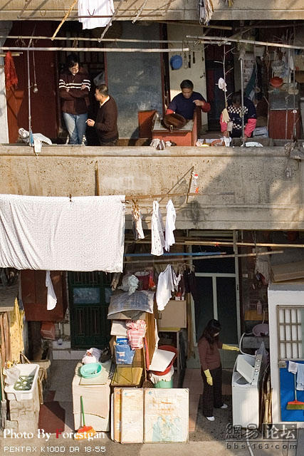 Neighbors on a balcony, while a housewife uses a washing machine below.