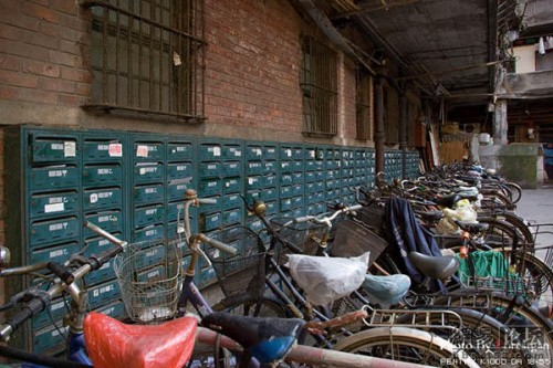 A row of bicycles and mail boxes in a courtyard building in Shanghai.