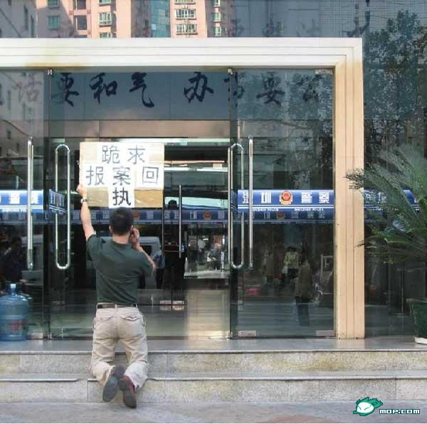 A Chinese man begs on his knees with a sign in front of a police station for help getting his passport back from a travel agency who refuses to return it.