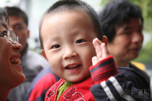 Chinese baby boy of migrant workers waves.