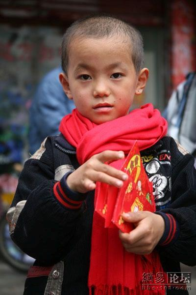 A young Chinese boy holds onto his red pockets or red envelopes of cash.