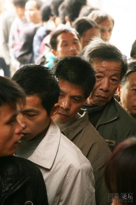 A line of Chinese migrant workers signing up for charity.