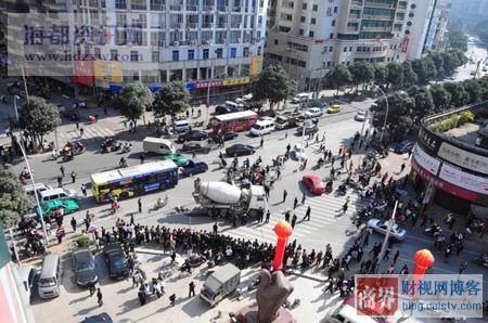 In Fuzhou, China, a crowd watches a terrible scene after a middle-aged woman is run over by a cement mixing truck at a busy intersection.