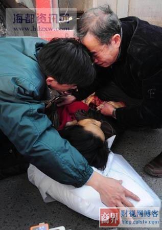 The husband and another elder cry above the Chinese woman who was run over.