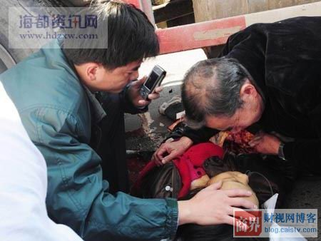 The older Chinese man cries as the victim's husband holds a cell phone and caresses her hair.