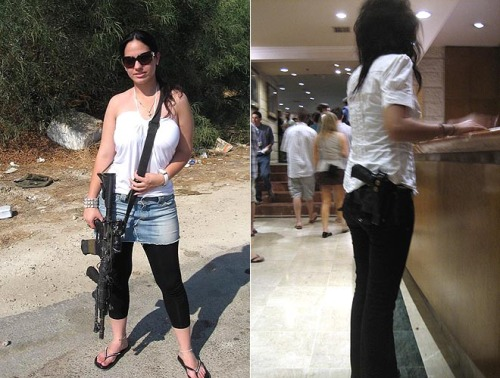 A Jewish girl poses for the camera with her machine gun. Another Jewish girl waits at a counter with a handgun on her waist.