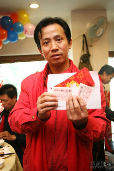 A migrant worker shows the free train tickets and cash the charity organization gave him to help him visit home for the holidays.