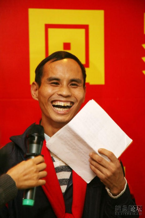 A migrant worker smiles while giving a speech thanking the charity organization.