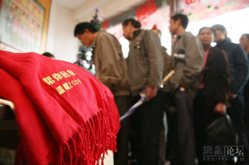 A red scarf with the Chinese words of 'help you return home' for the charity organization helping migrant workers return to their hometowns and families for Spring Festival.
