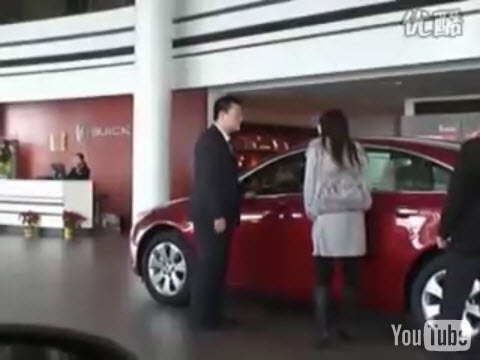 A video of a woman and man arguing in a Buick showroom in China about buying a Buick Regal. The man refuses so the girl gets in the car & begins driving around.