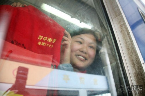 A migrant worker holds up a t-shirt of the charity organization that is helping her visit her family for the Chinese New Year holiday.