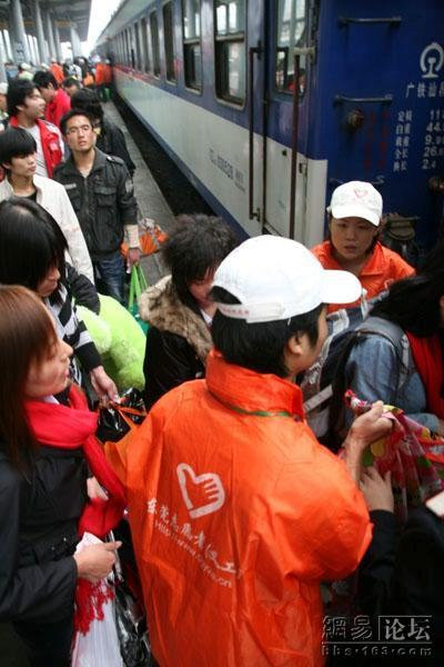 A volunteer helps migrant workers board the train home.
