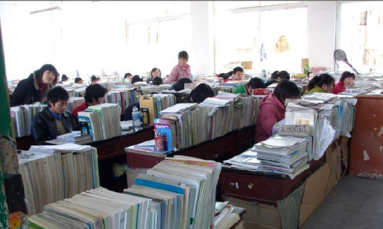 Pictures of Chinese high school students preparing for their university entrance examinations. Their desks are covered with textbooks & preparation materials.
