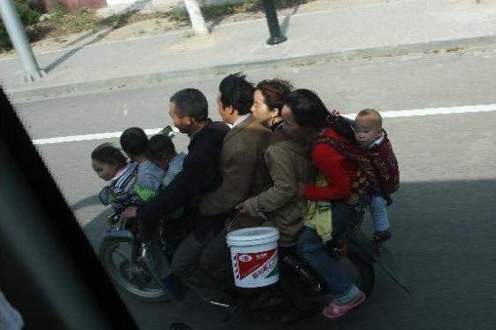 Pictures of 8 people including little children all riding a motorcycle together in China. Some say the poor have no choice. Some ask what brand of motorcycle?