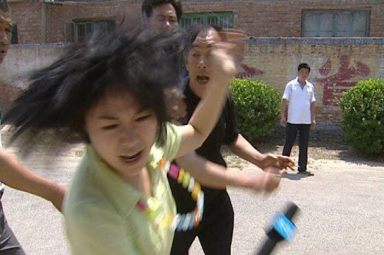 A television reporter is attacked by a corrupt village official in Shandong, China. As she is being hit, other government officials stand by and do nothing.