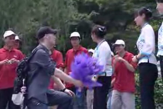A young foreigner proposes to a Chinese girl who rows a boat in Yangzhou, China...repeatedly, following her with flowers & signs asking her