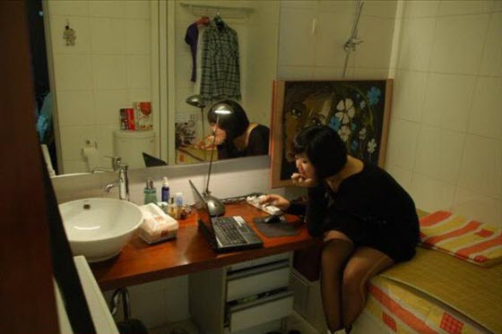 A post-80s generation pretty young Chinese woman lives in the toilet/bathroom of her company because housing prices are too expensive. Her bed is the bathtub.