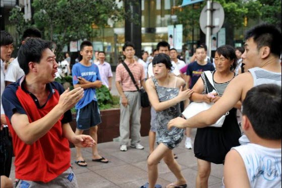 Photos of a violent fight between a man and a family over a seat on Shanghai's Nanjing Road pedestrian street tourist tram. The wife/mother seems very ruthless!