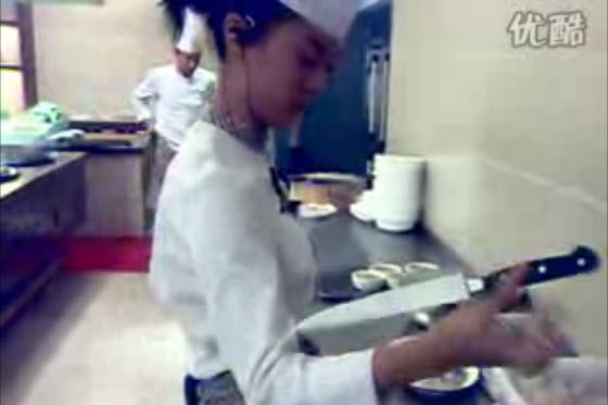 A short video of a young Chinese female chef showing off her knife tricks, spinning two big knives with both of her hands, in the kitchen of a restaurant.