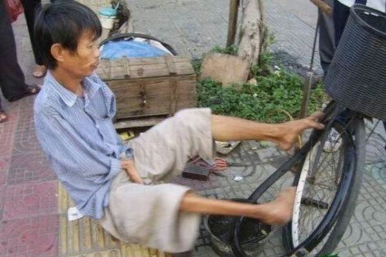 Photographs of a disabled & handicapped man with no hands in China making a living patching & repairing bicycle tires on the streets using only his crooked feet