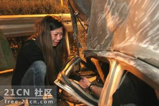 A young Chinese girl is seen crying, clutching the hand of her boyfriend, who is near death and trapped inside an overturned Chery QQ, begging him to hold on.