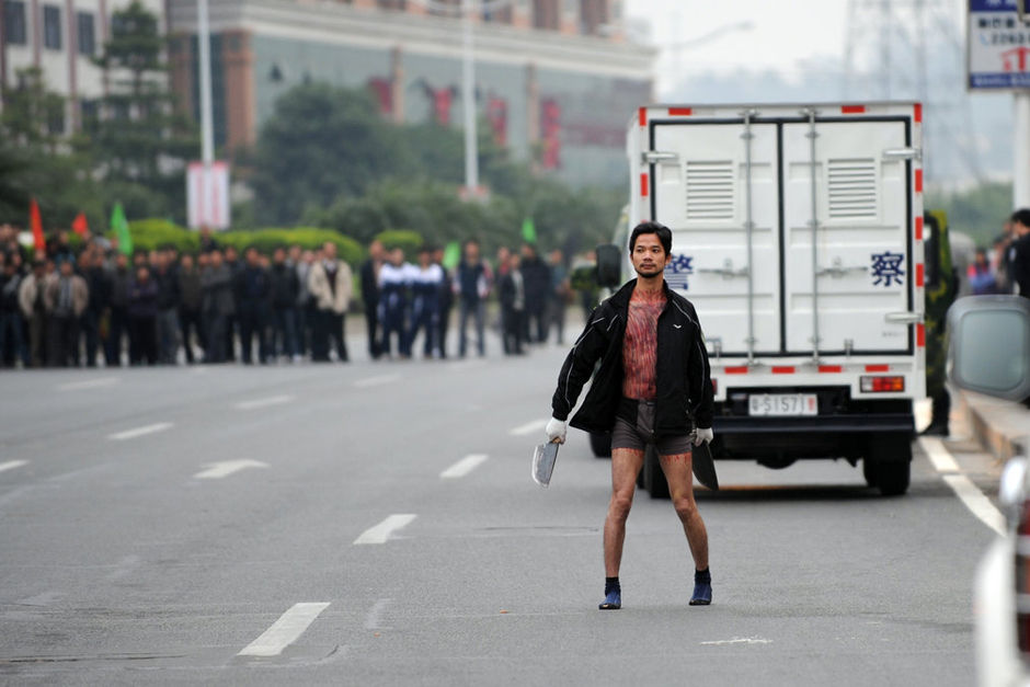 A half-naked Chinese man wielding two large cleavers in the middle of a street in Dongguan, Guangdong becomes internet famous for his expression and erection.
