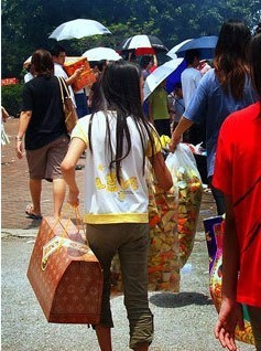 Asian girl carrying boxes and bags.