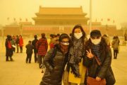 Three Chinese girls taking a photo in front of the Forbidden City during a Beijing sandstorm.