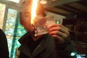 Chinese student lights a cigarette with a 100 RMB cash note.