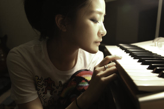 PixieTea (Zhang Xuanyan) beside piano keys.